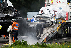 © Licensed to London News Pictures. 26/08/2017. Milton Keynes, UK. Part of the remains of the minibus on a recovery vehicle (right). The scene on the M1 motorway near Milton Keynes after a crash involving a minibus and two lorries. Police say that several people are dead and four others have been taken to hospital after the accident on the southbound carriageway in the early hours of this morning. Photo credit: Ben Cawthra/LNP