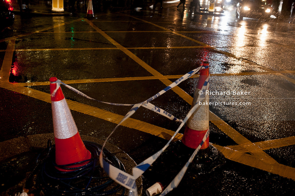 Police tape tangled between two trafic cones and a wet road surfaceon 12th January 2017, in central London, UK.