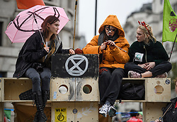 © Licensed to London News Pictures. 07/10/2019. London, UK. A group of Extinction Rebellion activists sit on a wooden structure in Trafalgar Square, Westminster. Activists will converge on Westminster blockading roads in the area for at least two weeks calling on government departments to 'Tell the Truth' about what they are doing to tackle the Emergency. Photo credit: Ben Cawthra/LNP