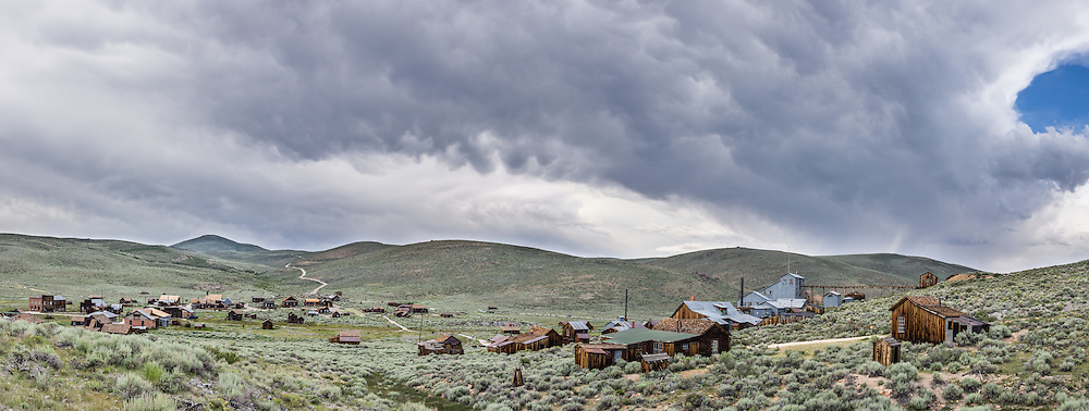 "Afternoon thunderstorm clouds loom over a panorama of historic Bodie and its Standard Stamp Mill. Bodie is California's official state gold rush ghost town. Bodie State Historic Park lies in the Bodie Hills east of the Sierra Nevada mountain range in Mono County, near Bridgeport, California, USA. After W. S. Bodey's original gold discovery in 1859, profitable gold ore discoveries in 1876 and 1878 transformed ""Bodie"" from an isolated mining camp to a Wild West boomtown. By 1879, Bodie had a population of 5000-7000 people with 2000 buildings. At its peak, 65 saloons lined Main Street, which was a mile long. Bodie declined rapidly 1912-1917 and the last mine closed in 1942. Bodie became a National Historic Landmark in 1961 and Bodie State Historic Park in 1962. This panorama was stitched from 4 overlapping photos."