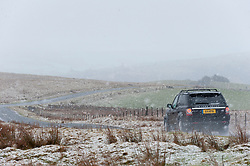 © Licensed to London News Pictures. 10/02/2019. Builth Wells, Powys, Wales, UK. A motorist drives along the B4520 (Brecon road) near Builth Wells through a wintry landscape on the Mynydd Epynt moorland in Powys, Wales, UK. credit: Graham M. Lawrence/LNP
