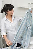Female housekeeper looking at shirt