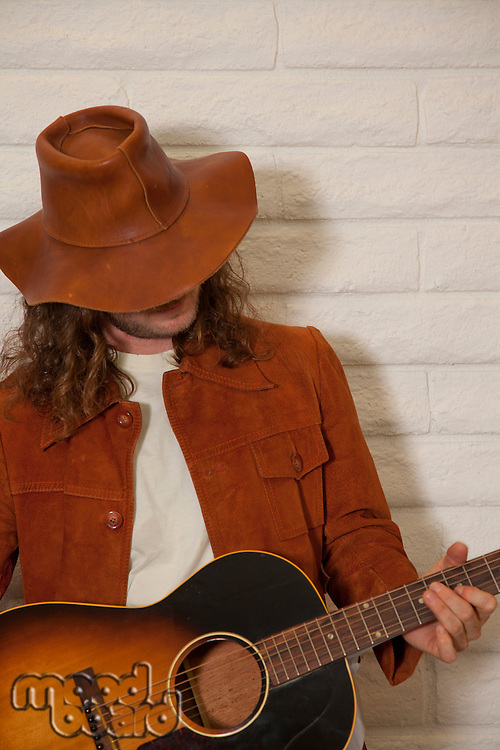 Mid adult man wearing cowboy hat and playing guitar