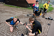 Tijdens de toertocht met het Paastreffen moet een lekke band van een tandem worden geplakt.<br /> <br /> During a tour with the Dutch Society of Human Powered Vehicles, one of the participants is being helped with a flat tyre on the tandem.