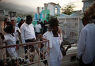 A worker hammers the coffin of Jean Estaveron Maymond, 77, in order for it to fit into a repurposed burial chamber, as family gather for his funeral at National Cemetery in Port-au-Prince, Haiti, Thursday, March 25, 2010.  The cemetery, made up of mostly above-ground tombs, was heavily damaged in the January 12 earthquake.
