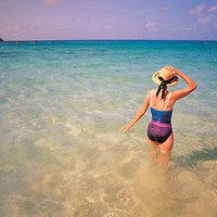 A woman holds onto her sun hat as she walks into the clear carribean waters off St. Bart's Island