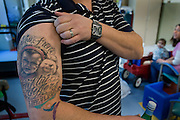 At the hospital,  with Malyia looking on,  Ryan Jeffers shows of a tattoo he got honoring Malyia and the life flight that saved her life.