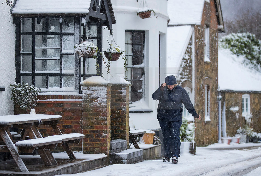 © Licensed to London News Pictures. 27/12/2017. Dorking, UK. A resident of Coldharbour braves the snow showers and low temperatures to visit the village shop - in the Surrey Hills. Photo credit: Peter Macdiarmid/LNP