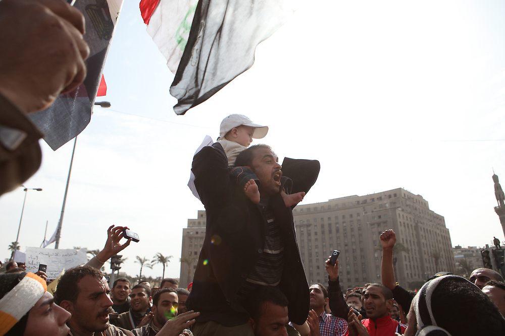 A protester at Tahrir Square carries a baby and chants for Hosni Mubarak's ouster.