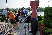 "20 FEBRUARY 2008 -- KANCHANABURI, THAILAND: Tourists pass a fake bomb as they cross the ""Bridge over the River Kwai"" in Kanchanaburi, Thailand. The infamous bridge and the ""Death Railway"" that connected Thailand and Burma were built by Japanese military forces using prisoner of war and slave labor during World War II. More than 200,000 POWs and laborers were used to build the railway, about half of them died during the construction.  Photo by Jack Kurtz"