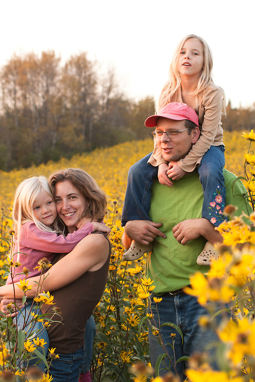 Manitoba family hiking in a crop of sunflower used for seeding.  Mother father and two young girls interacting.