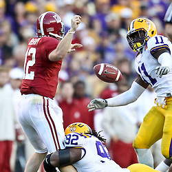 November 6, 2010; Baton Rouge, LA, USA;  Alabama Crimson Tide quarterback Greg McElroy (12) fumbles as he is hit by LSU Tigers defensive tackle Drake Nevis (92) during the second half at Tiger Stadium. LSU defeated Alabama 24-21.  Mandatory Credit: Derick E. Hingle