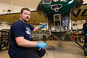 Kyle Bushman of Ragwood Refactory explains elements of aircraft restoration while working on an Interstate Cadet.
