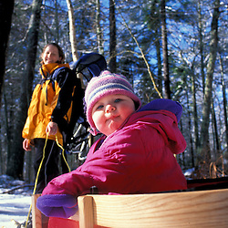 A young girl (age 2) is pulled in a toboggan by her mom at Maine's Rachel Carson National Wildlife Refuge in Wells, Maine. MR