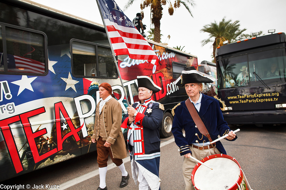 22 OCTOBER 2010 - PHOENIX, AZ:  Dr. LANCE HURLEY, left, as Patrick Henry, JOHN ROSADO, as a Continental Army soldier, and MITCH MARKOVIC, as a Continental Army drummer, lead the Tea Party Express bus into the grounds of the Arizona State Capitol Friday. About 300 people attended a Tea Party rally on the lawn of the Arizona State Capitol in Phoenix Friday. They demanded lower taxes, less government spending, repeal of the health care reform bill, and strengthening of the US side of the US - Mexican border. They listened to Arizona politicians and applauded wildly when former Alaska Governor Sarah Palin and her son, Trig, made a surprise appearance. The event was a part of the Tea Party Express bus tour that is crossing the United States.     Photo by Jack Kurtz