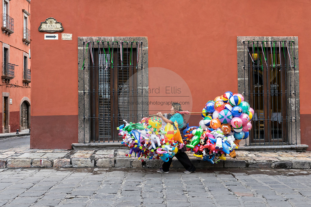 A Mexican balloon seller carries her wares on a pole through the streets of San Miguel de Allende, Mexico.