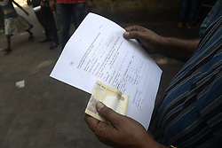 November 13, 2016 - Kolkata, West Bengal, India - Indian check the filled up from and hold Rs.500 bank note  in hand in front of a bank in Kolkata.To facilitate smooth exchange and deposit the old Rs. 500 and Rs. 1000 bank note bank across India remain open for public on Sunday , as announced by Union Government after demonetized Rs.500 and Rs.1000 bank notes to tackle the menace of black money. Indian line up outside the banks to deposit and exchange demonetized bank note from late night. (Credit Image: © Saikat Paul/Pacific Press via ZUMA Wire)