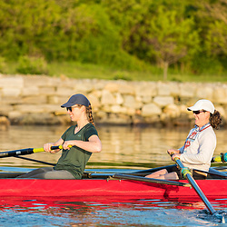 Two women rowing next to the Eastern Promenade in Portland, Maine. Casco Bay.