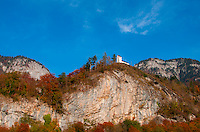 White chapel standing out against a blue sky and cliffs covered in autumnal-colored trees.  Glarus, Switzerland.