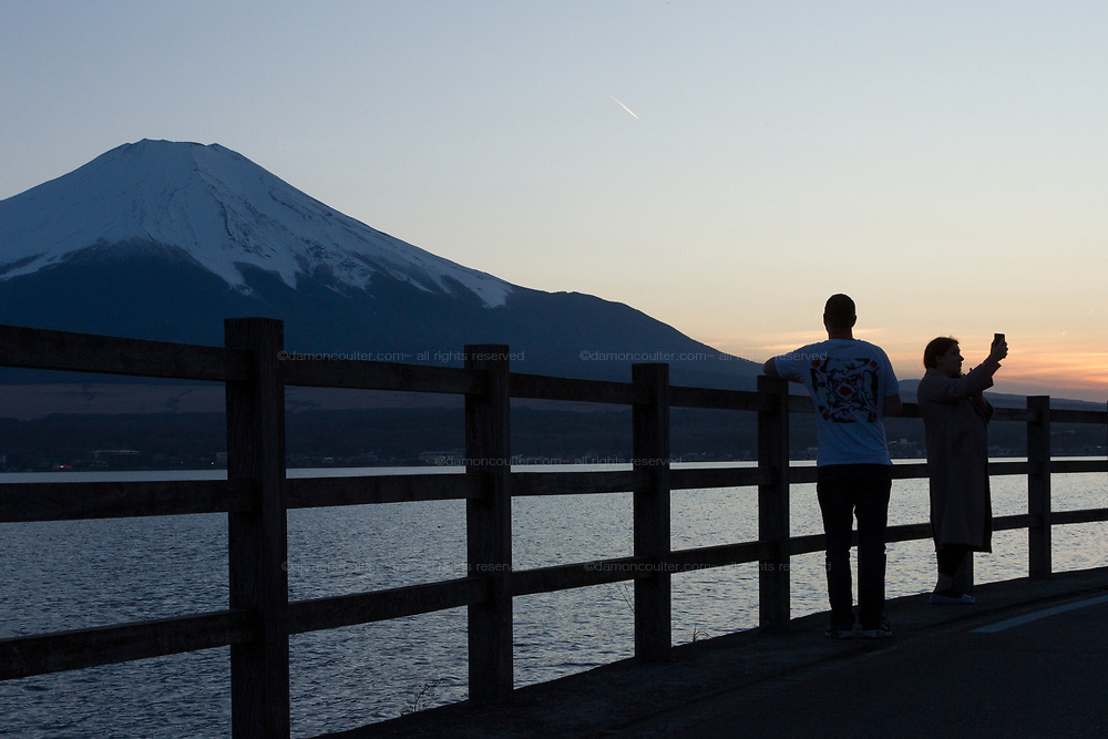 A Russian couple take selfies with Mount Fuji in the background, Lake Yamanaka, Yamanashi, Japan. Thursday March 26th 2020
