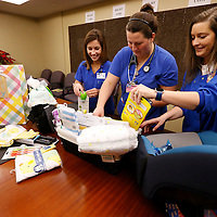 Thomas Wells | BUY AT PHOTOS.DJOURNAL.COM<br /> R.N.'s Olivia Bennett, from left, Mallary Covington and Tammy Tomilson begin wrapping up the gift package for the first baby baby born in 2017 at Baptist Memorial Hospital in New Albany.