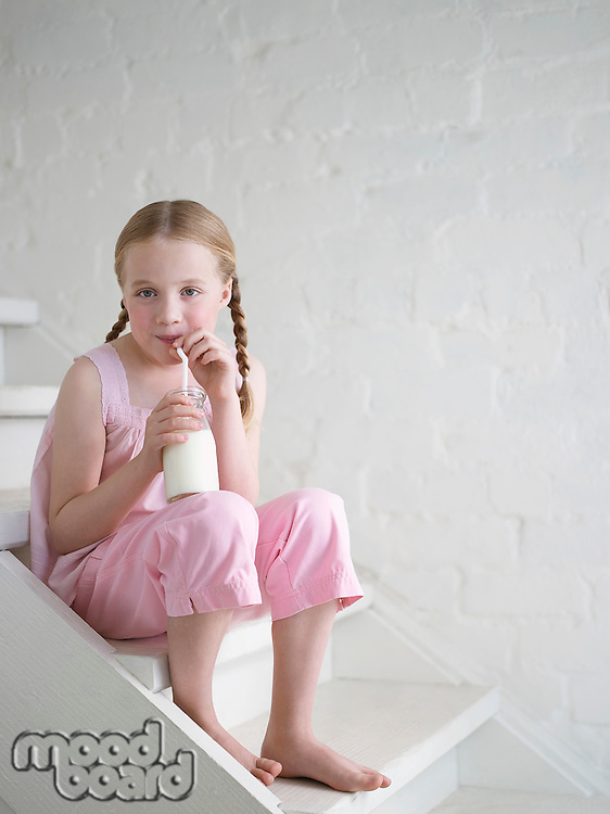 Barefoot Girl Drinking Glass of Milk sitting on stairs