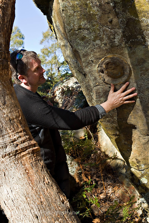 Geologist Andrew Ezzy observes sedimentary structures in Triassic Sandstone at Buckland, Tasmania, Australia