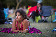 Kamora Johnson-Fisher, 7, waits for the movie Brave to begin during the 6th Annual District 4 National Night Out Resource Fair and Movie Night at Northwood Park in San Jose, California, on August 6, 2013. (Stan Olszewski/SOSKIphoto)