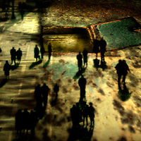 Silhouetted figures walking in an urban environment