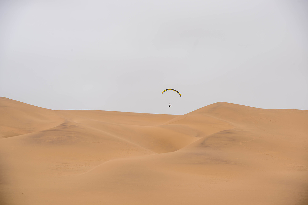 A parachuter floats above the sand dunes of the Namib desert, located in Namibia, Africa.