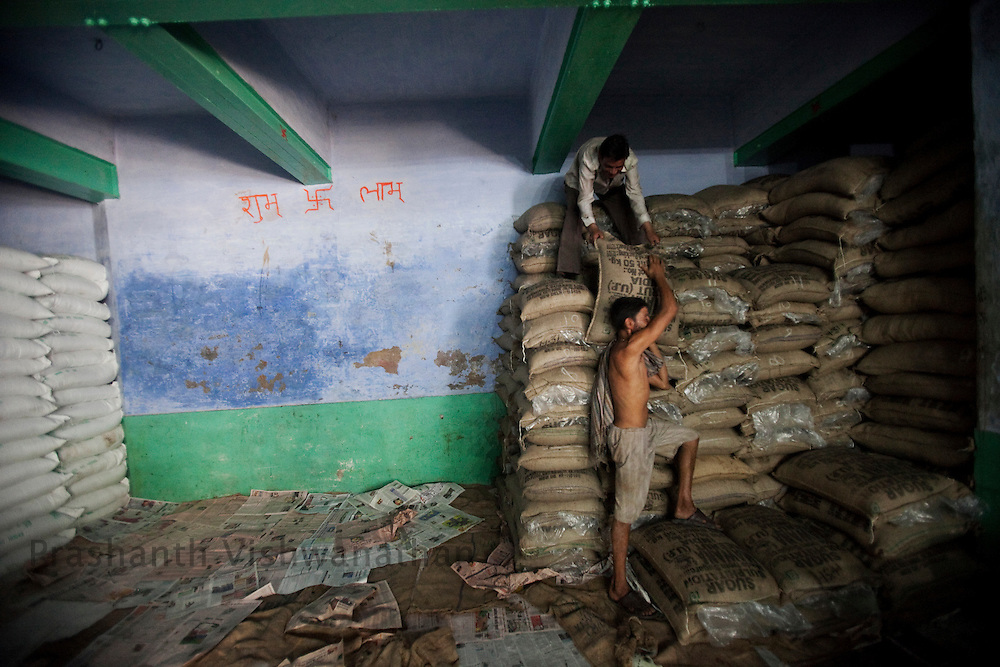 A labourer carries a 50 kg bag of sugar inside a godown of a distributor in the wholesale market of Old Delhi, in New Delhi, India, on Wednesday September 2, 2010. Photographer: Prashanth Vishwanathan/Bloomberg News
