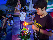 "17 NOVEMBER 2013 - BANGKOK, THAILAND: A woman lights the candle on her krathong before floating it in the Chao Phraya River at Wat Yannawa on Loy Krathong in Bangkok. Loy Krathong (also written as Loi Krathong) is celebrated annually throughout Thailand and certain parts of Laos and Burma (in Shan State). The name could be translated ""Floating Crown"" or ""Floating Decoration"" and comes from the tradition of making buoyant decorations which are then floated on a river. Loi Krathong takes place on the evening of the full moon of the 12th month in the traditional and they do this all evening on the 12th month Thai lunar calendar. In the western calendar this usually falls in November. The candle venerates the Buddha with light, while the krathong's floating symbolizes letting go of all one's hatred, anger, and defilements       PHOTO BY JACK KURTZ"