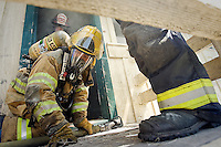 JEROME A. POLLOS/Press..Luke Nakamoto, a Northern Lakes volunteer firefighter, crawls out of house used to train new recruits on how to attack structure fires during training Saturday, June 28, 2008 in Hayden, Idaho.