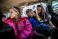 Megan buckles her little brother Titus into his seat next to their sister Ju Ju. Megan tries to take care of her younger siblings because she cannot  be their for two of her own younger sisters due to the way they were adopted.