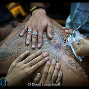 Devotees look on as others are given tattoos during festivities at the Wat Bang Phra tattoo festival in Nakhon Chai Si province on the outskirts of Bangkok, Thailand.