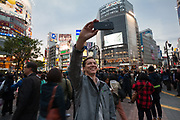 A western tourist takes a selfie with a smart phone at the iconic Shibuya Crossing Shibuya, Tokyo, Japan. Friday April 21st 2017
