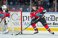 KELOWNA, CANADA - OCTOBER 28: Cal Foote #25 of the Kelowna Rockets skates with the puck from behind the net of James Porter #1 of the Kelowna Rockets against the Prince George Cougars on October 28, 2017 at Prospera Place in Kelowna, British Columbia, Canada.  (Photo by Marissa Baecker/Shoot the Breeze)  *** Local Caption ***