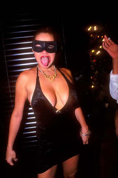 A masked woman at the door of a Miami Beach nightclub on Washington Avenue sticks out her tongue