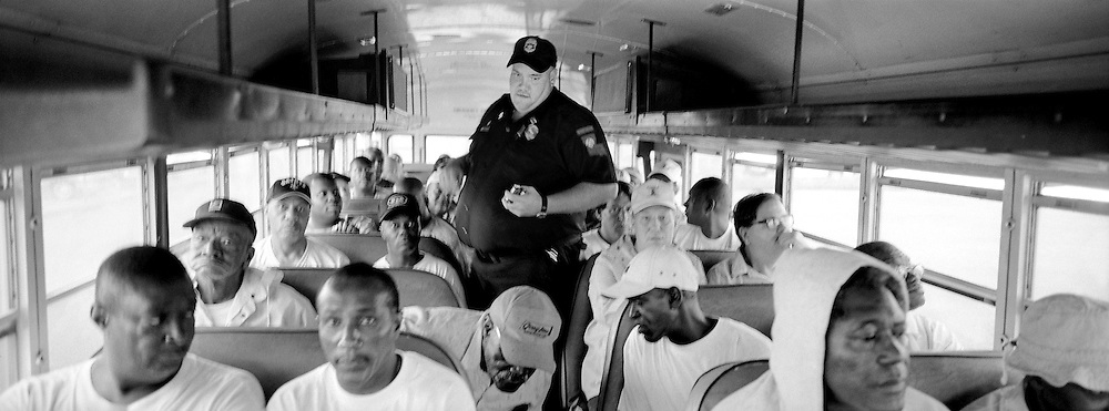 A prison security guard rides the bus with inmates as they travel to the prison cemetary for the burial of their fellow inmate George Alexander. The hospice volunteers program plans the memorial services and funerals for its patients. Once the service is over, however, the inmates return to their day-to-day life at the prison.