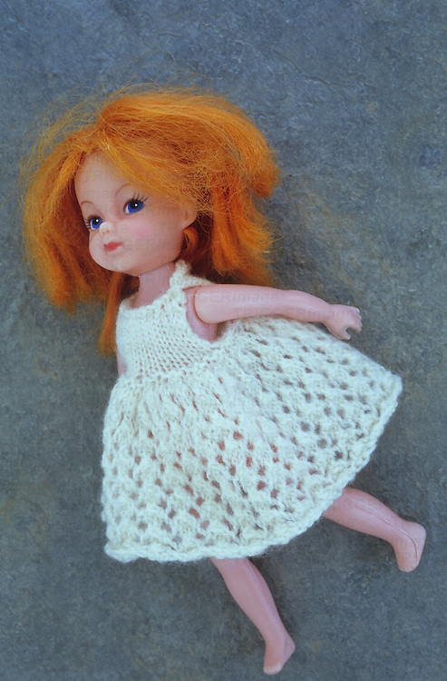 Modern girl doll with white knitted dress and ginger hair lying on her side on grey slate