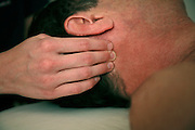 Man receiving massage to neck and shoulders during Swedish massage.