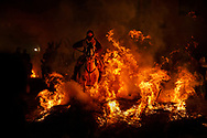 "A man rides a horse through a bonfire as part of a ritual in honor of Saint Anthony the Abbot, the patron saint of domestic animals, in San Bartolome de Pinares, west of Madrid, Spain on Monday, Jan. 16, 2017. On the eve of Saint Anthony's Day, hundreds ride their horses through the narrow cobblestone streets of the small village of San Bartolome during the ""Luminarias,"" a tradition that dates back 500 years and is meant to purify the animals with the smoke of the bonfires and protect them for the year to come. (AP Photo/Daniel Ochoa de Olza)"