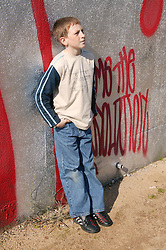 Boy leaning against a wall in a park,