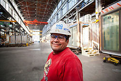 "Blu Homes construction workers inside their state of the art ""green"" LEED certifiable, prefab home Mare Island factory in Vallejo, California. The 250,000 square foot facility was previously used to build submarine periscopes when the US Navy was based there."