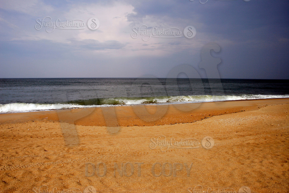 9 June 2006:  Atlantic Ocean beach scene along the Outerbanks in North Carolina after a passing storm. Surf crashes along the beach on wet sand and dark blue skies. Graphic, art, scenic view east coast.
