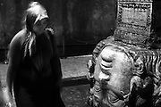 A woman passes by one of the two medusas heads in Basilica Cistern in Istanbul.