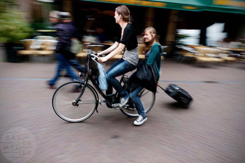 Een meisje zit achterop de fiets bij een ander meisje en houdt een koffer op wieltjes vast