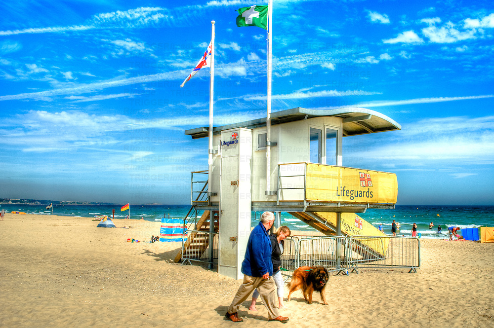 A beach watch tower people walking dog on beach