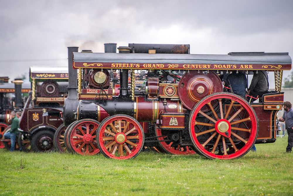 Side view of tractor steam engine parked on display in the rain, Masham, North Yorkshire, UK