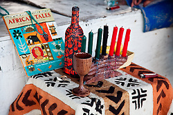 Traditional symbols of Kwanzaa.  Kikombe cha Umoja (The Unity Cup), Kinara (The Candle Holder), Mishumaa Saba (The Seven Candles), Mazao (The Crops), Mkeka (The Mat), and Zawadi(The Gifts)
